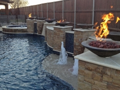 Free Form pool, Concrete Fire Bowls, Iridescent Glass Tile, Travertine and Stone Walls and Spa in Frisco (1)