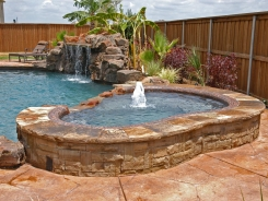 Stone Grotto and Raised Spa with Pebble Sheen in Prosper