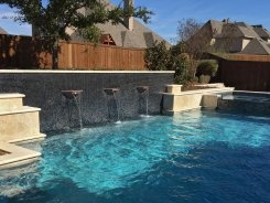 Geometric pool, Copper Water Bowls, Iridescent Glass Tile and Travertine Walls and Spa in Allen