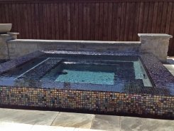 Iridescent Glass Tile Perimeter Overflow Spa with Blue Granite Pebble Sheen in Frisco