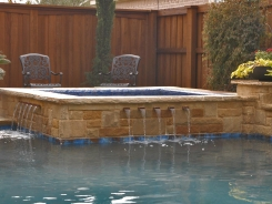 Iridescent Glass Tile Spa and Brass Spillways with Ocean Blue Pebble Sheen in Allen