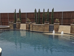 Free Form Pool, Bubblers, Sheer Descents Ocean Blue Pebble Sheen with Stone Walls and Columns in Frisco