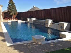Geometric Pool with Travertine and Glass Tile Raised Bond Beam with mediterranean quartz in Allen