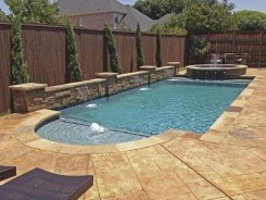 Geometric pool, Raised Bond Beam, Stone Scuppers with Aqua Blue Pebble Sheen in Frisco