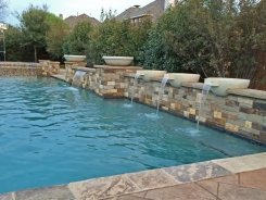 Geometric pool, Raised Bond Beam, Stone Water Bowls with Aqua Blue Pebble Sheen in Frisco (1)