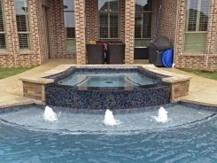 Iridescent Glass Tile Spa with Aqua Blue Pebble Sheen and Bubblers in Prosper