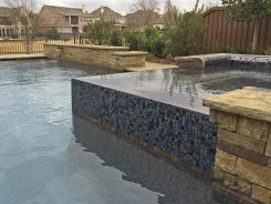 Iridescent Glass Tile Spa with Pebble Sheen and Brass Spillways in Frisco